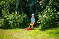 与从事园艺的愉快的小男孩帮助与他的割草机 免版税库存照片