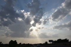 与从云彩出来的阳光光芒的剧烈的天空 库存图片