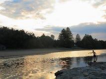 与年轻人渔的河风景由黄昏 免版税库存图片