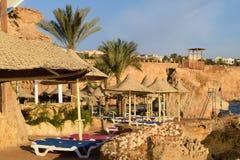 与轻便折叠躺椅和茅屋顶的埃及旅馆海滩 免版税库存图片