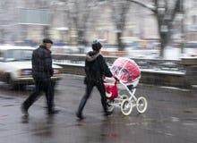与婴儿推车的家庭在斑马线 免版税库存图片