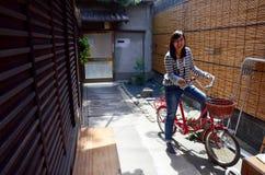与经典红色自行车的泰国妇女画象 库存图片