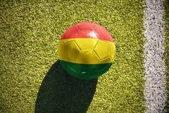 与玻利维亚的国旗的橄榄球球在领域说谎 图库摄影