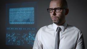 与财务和宏指令经济的未来工作 商人与一个交互式全息照相的屏幕一起使用 股票录像