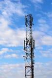 与移动电话天线的通讯台在多云天空背景 免版税库存照片