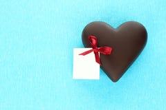 与贺卡的巧克力心脏在蓝色背景 免版税库存图片