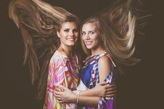 与头发的微笑的两个白肤金发的少妇秀丽画象在mot 库存照片