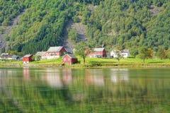 与绿叶,房子,水反射的不可思议的自然风景 免版税库存图片