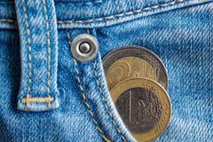 与1和两在破旧的蓝色牛仔布牛仔裤的口袋的欧元的衡量单位的两枚欧洲硬币 库存图片