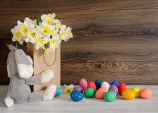 与水仙和在木背景的滑稽的兔宝宝可爱的花束的五颜六色的复活节彩蛋在纸袋的 免版税图库摄影