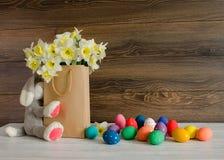与水仙和在木背景的滑稽的兔宝宝可爱的花束的五颜六色的复活节彩蛋在纸袋的 库存照片