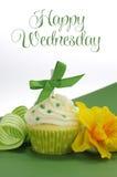 与黄水仙和条纹丝带的美丽的绿色装饰的杯形蛋糕在与愉快的星期三的绿色背景抽样文本 免版税库存照片