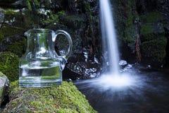 与水和瀑布的玻璃玻璃水瓶在背景中 免版税图库摄影