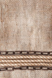 与绳索和金属链子的粗麻布背景 库存图片