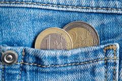 与1和2在破旧的老蓝色牛仔布牛仔裤的口袋的欧元的衡量单位的两枚欧洲硬币 免版税库存图片