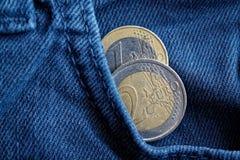 与1和2在蓝色牛仔布牛仔裤的口袋的欧元的衡量单位的两枚欧洲硬币 库存图片