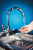 与水和洗涤的手的明三联式浴缸水嘴 免版税库存照片