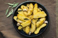 与贤哲叶子和大蒜的烤鱼种土豆 免版税库存照片