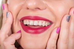 与嘴唇和手指的愉快的妇女面孔有波兰钉子的 演播室照片写真 图库摄影