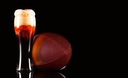与黑啤酒泡沫的啤酒杯和在黑背景的橄榄球球 免版税库存图片
