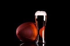 与黑啤酒泡沫的啤酒杯和在黑背景的橄榄球球 免版税库存照片