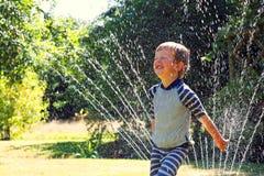 与水喷水隆头的夏天乐趣 库存照片