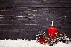 与黑土气木板的红色灼烧的蜡烛 免版税库存图片