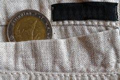 与10在亚麻布裤子的口袋的泰铢的衡量单位的泰国硬币有黑条纹的标签的 免版税库存照片
