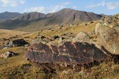 与刻在岩石上的文字的山由亚洲游牧人。纳伦 库存图片