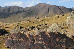 与刻在岩石上的文字的山由亚洲游牧人 免版税图库摄影