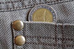 与10在棕色牛仔布牛仔裤的口袋的泰铢的衡量单位的泰国硬币 免版税库存照片