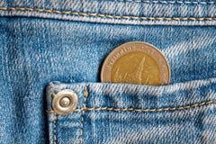 与10在浅兰的牛仔布牛仔裤的口袋的泰铢的衡量单位的泰国硬币 库存图片