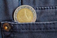 与10在灰色牛仔布牛仔裤的口袋的泰铢的衡量单位的泰国硬币 免版税图库摄影