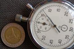 与10在破旧的牛仔裤背景-企业背景的泰铢(后部)和秒表的衡量单位的泰国硬币 图库摄影