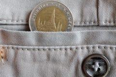 与10在米黄牛仔布牛仔裤的口袋的泰铢的衡量单位的泰国硬币有按钮的 免版税库存图片