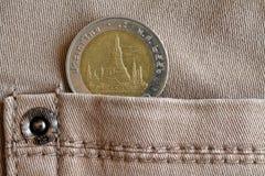 与10在米黄牛仔布牛仔裤的口袋的泰铢的衡量单位的泰国硬币 免版税库存照片