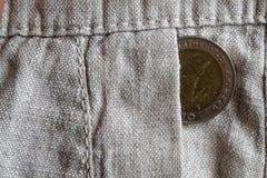 与10在老亚麻布裤子的口袋的泰铢的衡量单位的泰国硬币 库存照片