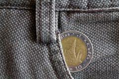 与10在老棕色牛仔布牛仔裤的口袋的泰铢的衡量单位的泰国硬币 免版税库存照片