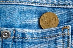 与10在老被穿的蓝色牛仔布牛仔裤的口袋的欧分的衡量单位的欧洲硬币 免版税图库摄影
