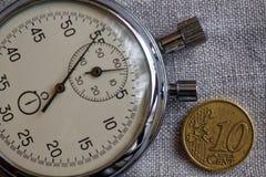 与10块欧分和秒表的衡量单位的欧洲硬币在白色亚麻制背景-企业背景 免版税库存图片