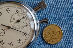 与10块欧分和秒表的衡量单位的欧洲硬币在蓝色牛仔布背景-企业背景 免版税库存图片
