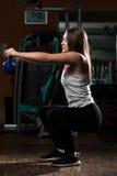 与水壶响铃的运动妇女锻炼 免版税库存图片