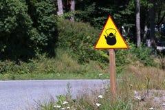 与水壶的黄色在路一边的标志或茶壶 库存照片