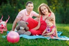 与年轻女儿的已婚夫妇坐地毯ipark 图库摄影