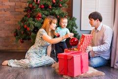 与婴孩的圣诞节家庭 愉快的儿童开头礼物 圣诞节我的投资组合结构树向量版本 图库摄影