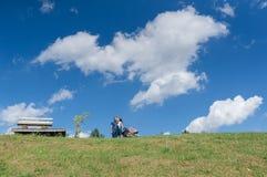 与婴孩的愉快的家庭领域的 下蓝色域绿色天空 夏天横向 免版税库存照片