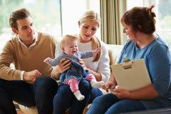 与年轻婴孩的社会工作者参观的家庭 库存图片