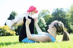 与婴孩的年轻母亲训练 免版税图库摄影
