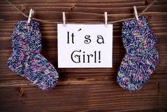 与婴孩袜子的桃红色标签和它女孩 免版税库存图片