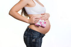 与婴孩赃物的孕妇的腹部 免版税库存图片